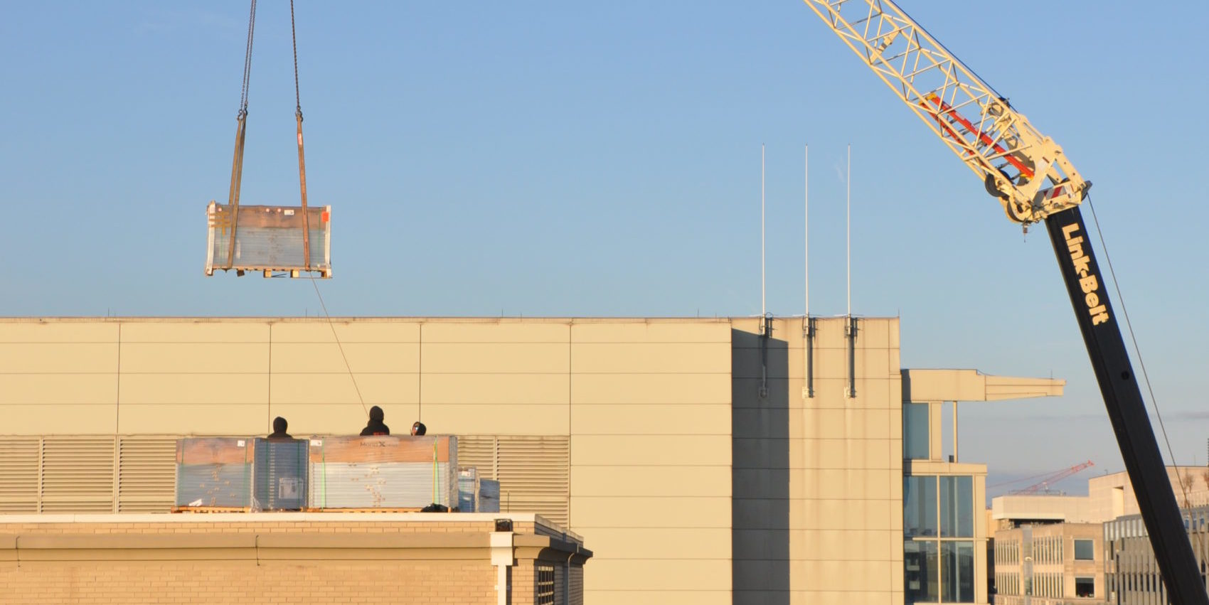 Three people are standing behind panels packages of panels on top of a building. A crate suspended by a crane is above them. Behind them is a building and to the right is the crane. Buildings are in the backdrop on the right and there is a clear, bright sky.