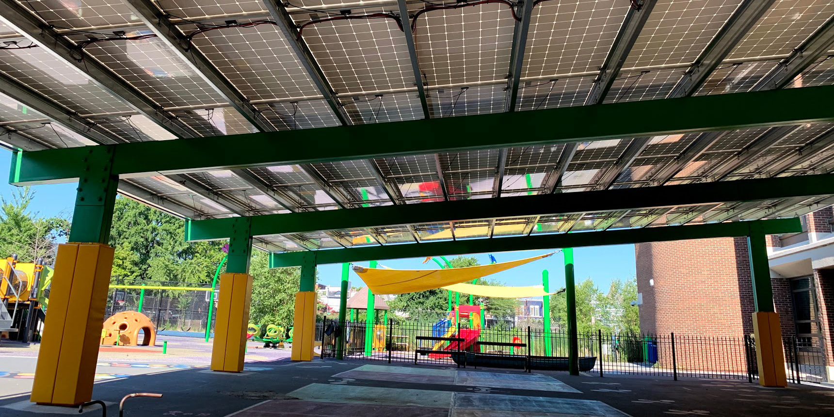 An eye-level view of Ludlow-Taylor Elementary School's solar panel roof. The photo appears to be taken under the roof and the four-square chalk area on the concrete is in front. Supportive pillars are on the left as well as a playground. Another playground set is in the backdrop behind a short iron fence. To the right is a brick building and further behind are trees, buildings, and a clear, sunny sky.