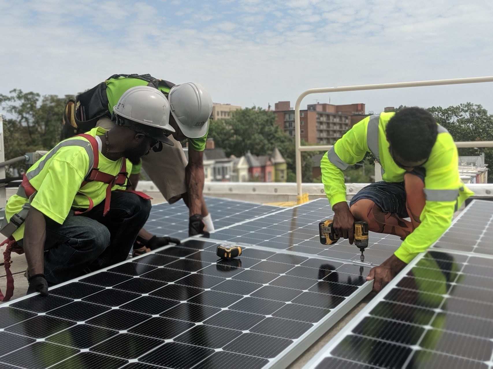 Three people standing on a rooftop around solar panels. Two are wearing construction hats to the left and the person on the right is holding a drill. They are all wearing neon safety shirts. The backdrop has trees, houses, buildings, and the sky is partially cloudy but parts of it are bright.