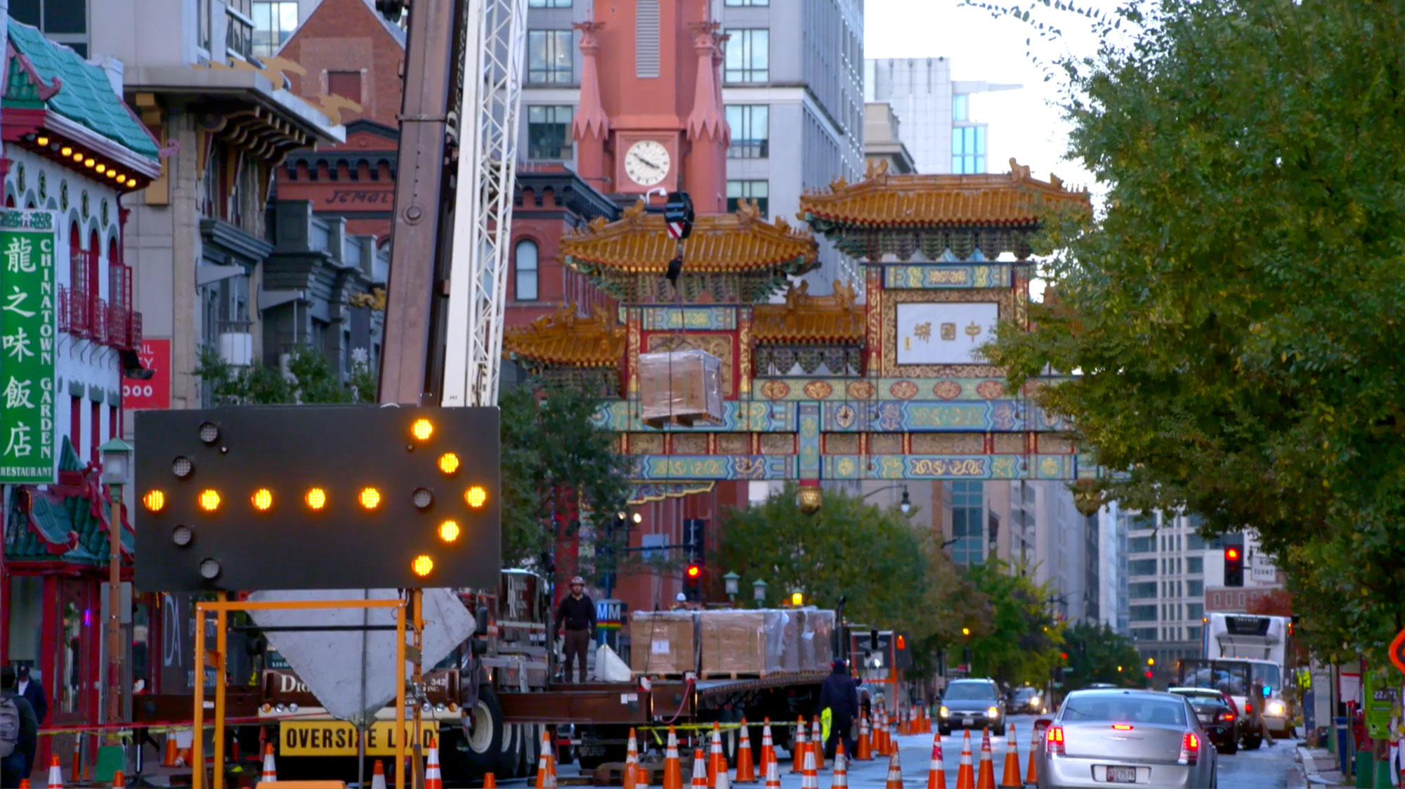 A neon construction arrow sign points right in front of a crane. The sign and crane are outside in front of a Chinatown community gate with many orange cones surrounding the crane. A sign to the left says 'Chinatown Garden Restaurant' and beyond the gate is a clock tower with four conical small towers surrounding the actual clock, and glass-paned buildings are behind the Chinatown community gate. There are cars on the road and trees lining the streets. The sky is bright with no outlines of clouds.